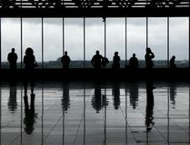 Observation deck - 1. Silhouetted people against the windows of an airport observation deck. The greyish floor and clouded day gives it a very monochrome aspect stock image