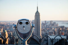 Observation Deck binoculars. Top of the rock observation deck with out of focus empire state building in the background stock photo