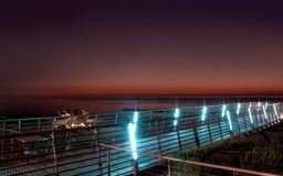 Observation deck over the sea at sunset. Observation deck over the sea illuminated by neon lights at sunset stock photos