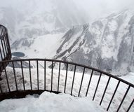 Observation deck for tourists along the Georgian military road in spring during heavy snowfall. Snowy landscape along the Georgian military road in spring during royalty free stock image