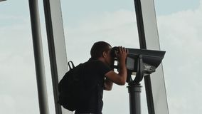 Tourist looking through binoculars on observation deck in tower Ho Chi Minh city. Observation deck tower in Ho Chi Minh city with tourists stock video footage