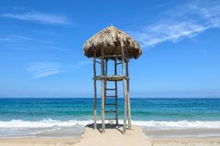 Observation post covered with dry palm leaves at the beach Royalty Free Stock Photos