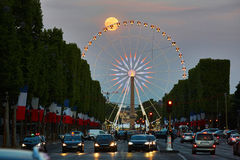 Observation wheel on Champs-Elysees street with full moon in Paris. Observation wheel on Champs-Elysees street with full moon in the sky in Paris, France royalty free stock photo