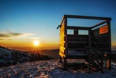 Observatoire d'oiseau au coucher du soleil sur la neige Photo libre de droits