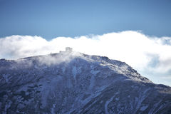 Observatory on the mountain Pip Ivan in clouds. Abandoned snow-covered observatory on the mountain Pip Ivan, called White Elephant in the Carpathian mountains Stock Photo