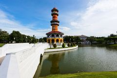 Observatory tower at Bang Pa In palace. Colorful observatory tower, called Ho Withun Thasana, with clear blue sky and white cloud and skyline reflection on the Stock Photography