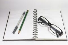 Observe los vidrios con el cuaderno del lápiz, de la pluma y de la carpeta aislado en el fondo blanco Imagen de archivo