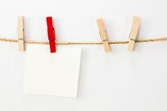 Observe o cartão, o Livro Branco e os grampos da madeira Imagens de Stock Royalty Free