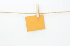 Observe o cartão, o papel marrom e os grampos da madeira Fotografia de Stock Royalty Free
