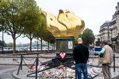 Observers stand by Flame of Liberty in Paris as unofficial memor. In 2012, wreaths are left at the base of the Flame of Liberty (Flamme de la Liberte) in early Stock Photography