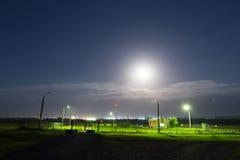 Observez la maison sous la lumière de la lune la nuit Photo stock