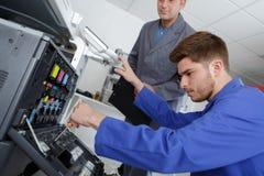 Observing apprentice fix printer. Observing an apprentice fix a printer Royalty Free Stock Image