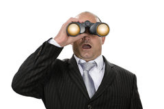 Observing. Businessman watching observing something stunning with binoculars Stock Photography
