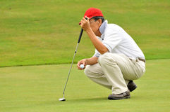 Observing the contours of the green. Senior golfer is assessing the contours of the green Royalty Free Stock Photos