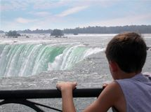 Observing the falls. Young boy observing niagara falls royalty free stock photography
