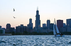 Observing the Sunset. A lone sailboat against the dramatic skyline of Chicago at sunset Stock Image