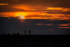 Observing sunset. Woman and man observing sunset from  breakwater Royalty Free Stock Photos