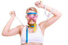 Obsessed fitness woman with a lot of colorful measure tapes Royalty Free Stock Photo