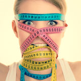 Obsessed girl by your body. Woman with measure tapes. Royalty Free Stock Image