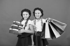 Obsessed with shopping and clothing malls. Shopaholic concept. Shopping become fun with best friends. Kids cute. Schoolgirls hold bunch shopping bags. Children stock photography