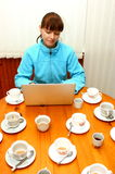 Obsession. A woman working on a laptop (computer) and many coffee (tea) cups (mugs), on a wooden table royalty free stock photos