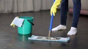 Obsessivo com a jovem senhora da limpeza que lava completamente o assoalho de sua casa imagem de stock