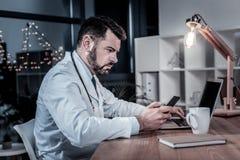 Obsiadła wykwalifikowana lekarka trzyma telefon komórkowego używać laptop obraz royalty free