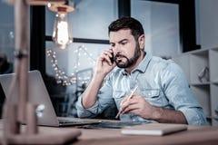 Obsiadły rzetelny pracownik ma rozmowę telefoniczną i używa jego laptop zdjęcia royalty free