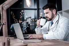 Obsiadły studenta medycyny pić herbaciany i używać laptop obraz stock