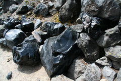 Obsidian boulders from lava flow Royalty Free Stock Image