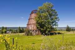 Old abandoned obsolete sawdust burner. An obsolete abandoned sawdust burner standing in a field with flowers Royalty Free Stock Photo