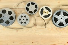 Obsolete cinema films on wooden surface of table. Royalty Free Stock Photo