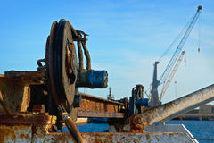 Obsolete equipment on a background of modern cranes Stock Photo