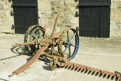 Obsolete farm equipment. An old obsolete reaper machine standing in the farm yard in front of the barn doors Royalty Free Stock Photos