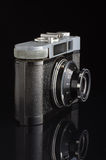 Obsolete film camera isolated on the dark background with reflection Stock Photo