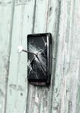 Obsolete mobile phone is nailed to a wooden fence stock image