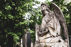 Obsolete old stature of angel with cross on burial on cemetery in Lychakiv Cemetery, Lviv royalty free stock photos