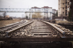 Obsolete rails. Obsolete peace of rails with a bridge in the background Royalty Free Stock Photo