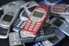 Obsolete red cell phone in pile. Pile of unwanted old mobile cell phones. Bright red phone on top of pile. No logos visible royalty free stock image