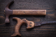 Obsolete rough handsaw and claw hammer on vintage wooden board Royalty Free Stock Photos