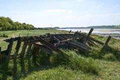 Historic tidal river bank erosion protection scheme at Purton Hulks, Gloucestershire, UK. Obsolete small boats and barges were stranded on the banks of the tidal stock images