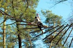 Obstáculos del surmountain de la mujer en el parque de la cuerda Foto de archivo libre de regalías
