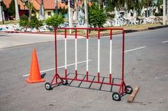 Obstáculos rojos y blancos de la señal de tráfico del bloqueo en el camino con la naranja Fotos de archivo