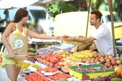 Obst-und Gemüsehändler, der eine Frucht zu einem Verbraucher austeilt. stockbild