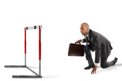 Obstacle on the business road. Businessman ready to race looks an obstacle Royalty Free Stock Photography