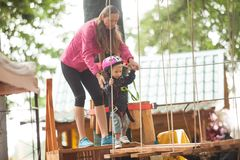 The obstacle course in adventure park. Kids on obstacle course in adventure park in mountain helmet and safety equipment stock images