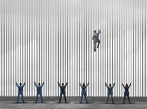 Obstacle To Opportunity. Concept as a group of people as businessmen and businesswomen locked behind prison bars with one individual smart business leader using Stock Photography