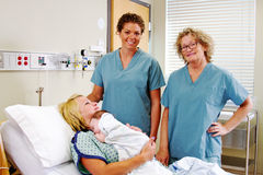 Obstetric nurses with Mom and newborn stock image