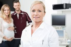 Obstetrician With Expectant Couple In Background. Portrait of mid adult female obstetrician with expectant couple standing in background Royalty Free Stock Photography