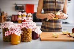 Obstkonserven in den Glasgefäßen mit der Frau, die Apfel viertelt Lizenzfreies Stockfoto